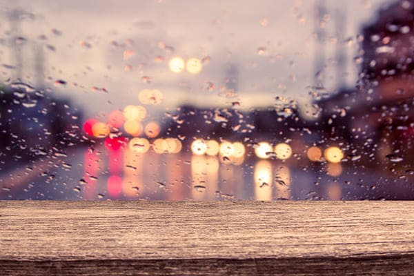 Blick aus dem Fenster, bei einem regnerischen Tag mit Vehrkehr im unscharfem Hintergrund.