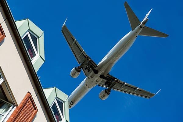 Flugzeug fliegt sehr nah über ein Haus vorbei. Hausseite mit vielen Fenstern, die mit Schallschutzscheiben versehen sind.