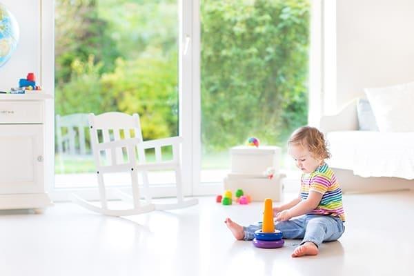 Kind spielt im Wohnzimmer auf dem Boden im Hitergrund große Fensterfront.