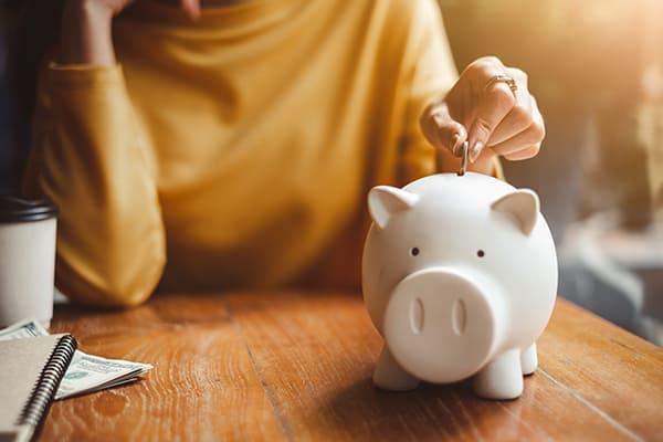 Frau schmeißt Geldstück in ein Sparschwein.