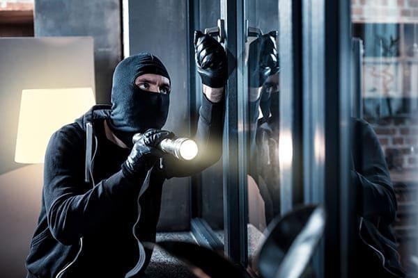 Einbrecher ist vor dem Fenster innen und macht es leise zu.
