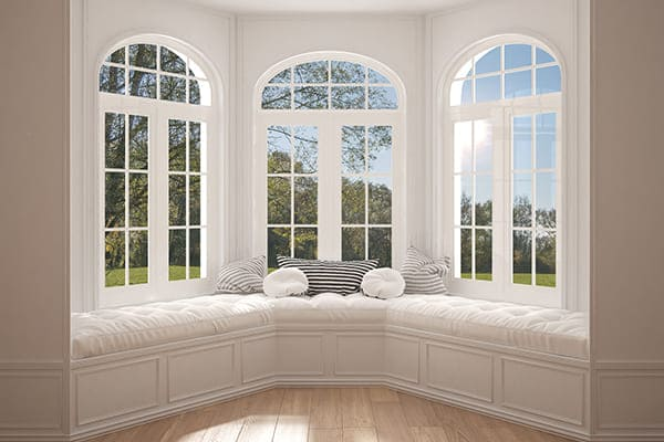 Große Erkerfensterfront mit Rundbogenfenster oben.