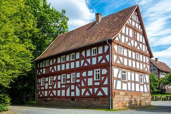 Großes Fachwerkhaus mit roten Balken und weißen Kunststofffenstern.