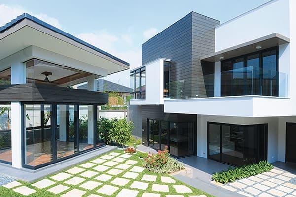 Zwei Häuser mit großen anthrazitfarbenen Fensterelementen