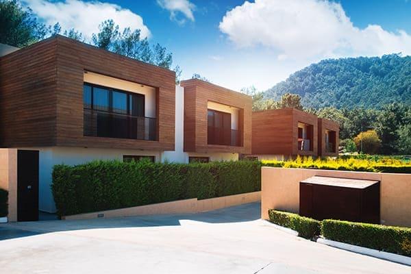 Moderne Häuser mit grüner Pflanzenwand und schwarzen Fenstern mit Aluschale außen.