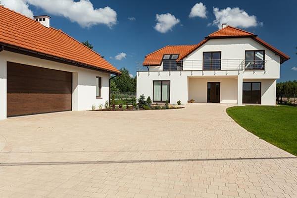 Große Einfahrt mit Haus im Hintergrund und Garagen auf der linken Seite.
