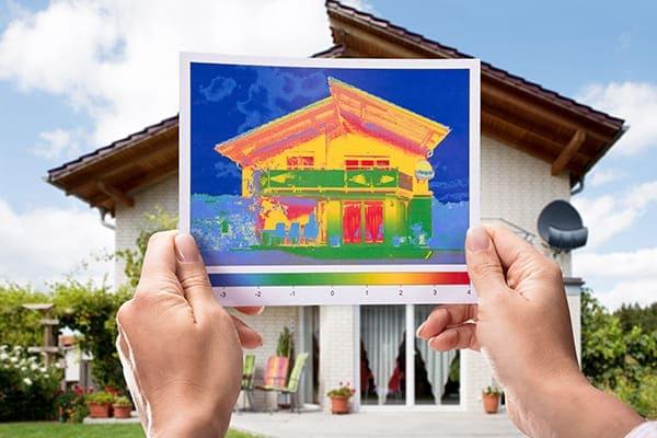 Wärmebild wird vor das Wohnhaus von einer Frau gehalten.