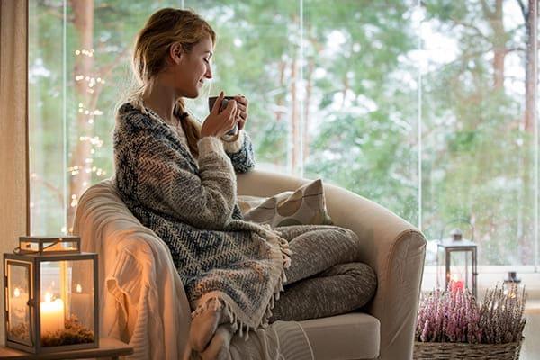 Frau sitz im Sessel mit Decke und trink einen Tee vor einer großen Fensterfront.