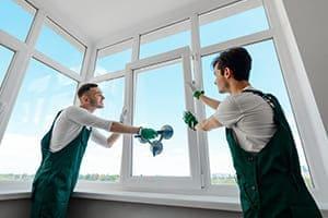 Zwei Fenstermonteure setzten einen Flügel in den Fensterrahmen ein. Fensterfront hat mehrere Oberlichter.
