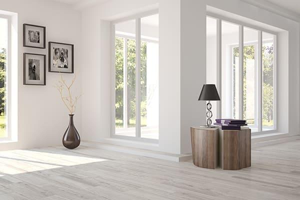 Weißes Zimmer mit Möbeln und grüner Landschaft im Fenster