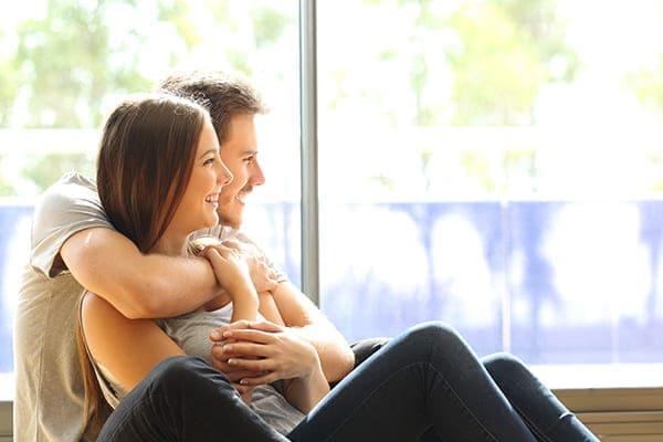 Ehepaar oder Ehe in seinem neuen Zuhause mit Blick durch das Fenster