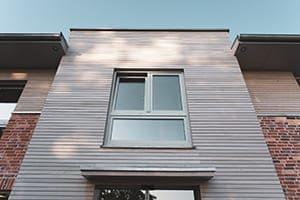 Haus von außen wo Fenster mit Unterlicht zu sehen sind.