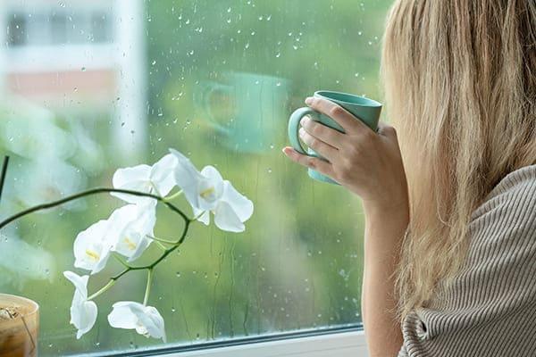 Frau mit Tasse vor Fensterscheibe