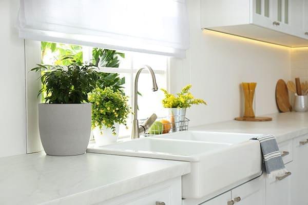 schöne helle Küche mit Fenster hinter der Spüle.