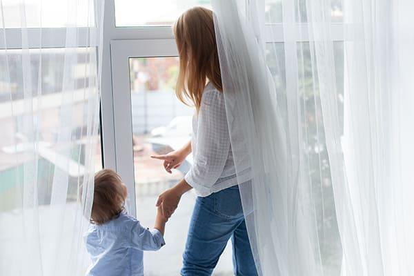 eine Frau steht an einem großen Fenster mit ihrem  Sohn und blickt aus dem Fenster