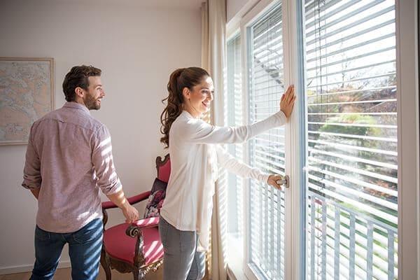 Paar steht in Wohnzimmer und schließt Fenster