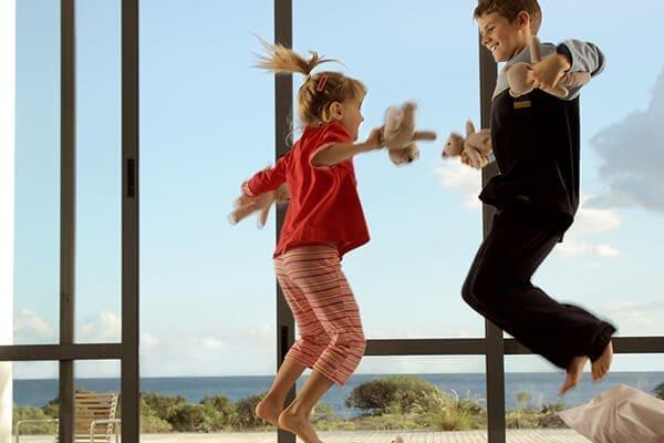 Kinder springen auf Bette im Hintergrund große Fensterfront