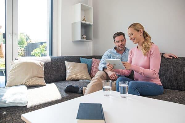 Paar sitzt auf der Couch mit Tablet