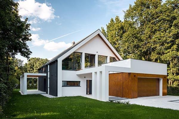 Modernes Haus von außen gesehen mit Garten und vielen unterschiedlichen Fenstertypen.