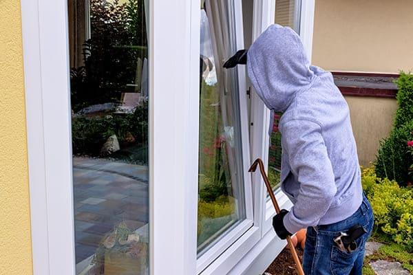 Einbrecher versucht ein gekipptes Fenster zu öffnen.