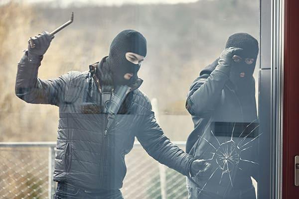Zwei Einbrecher versuchen die Scheibe von einzuschlagen.