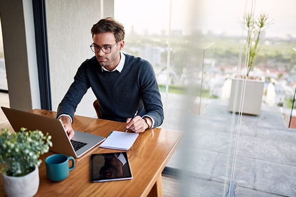Mann sitzt vor dem Laptop und konfiguriert seine Fenster auf der Internetseite FensterHandel.de.