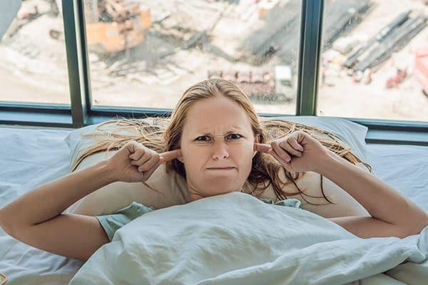 Frau liegt im Bett und hält sich die Ohren zu, im Hintergrund große Fensterscheiben.