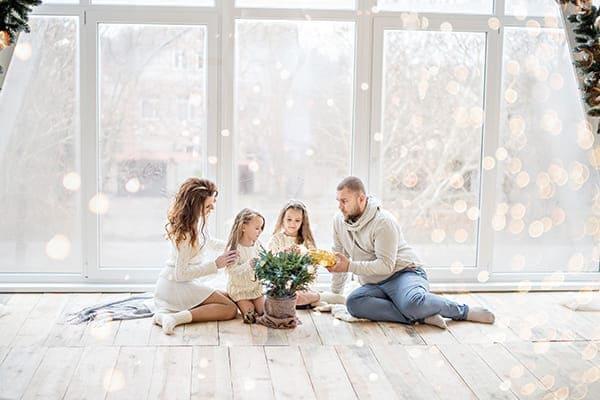 Familie sitzt auf dem Boden vor einer großen Fensterfront mit Winterlandschaft im Hintergrund.