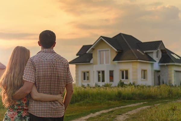 Ehepaar sehen sich Ihr Haus mit vielen verschiedenen Fenstertypen von außen an.