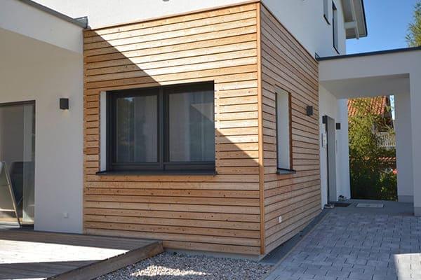 Schönes modernes Haus von außen gesehen mit anthrazitfarbenen Fenstern.