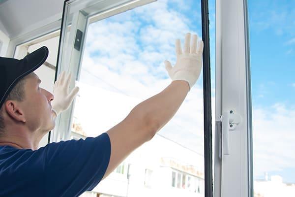 Meister in Schutzhandschuhen, Wechseln eines doppelt verglasten Fensters in einem Kunststofffenster.
