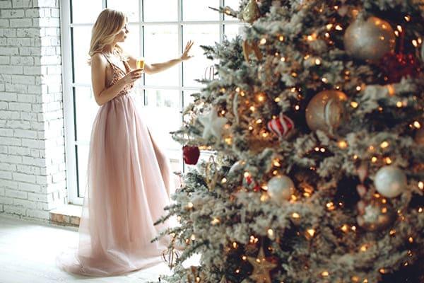 Frau in einem schönen Kleid, steht vorm Fenster mit Sektglas.