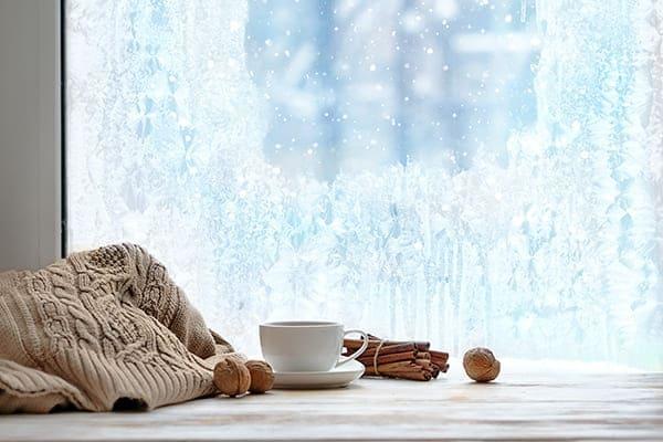 gefrorenes Fenster mit Tee, Zimt und Nüssen auf dem Fensterbrett.