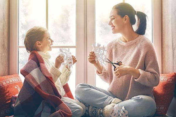 Liebevolle Familie sitzend am Fenster und machen Papier Schneeflocken für die Dekoration Fenster.