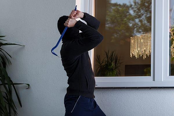 Einbrecher will Fensterscheibe einschlagen.