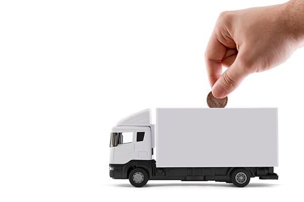 Mann schmeißt Münze in weißen Lastwagen.