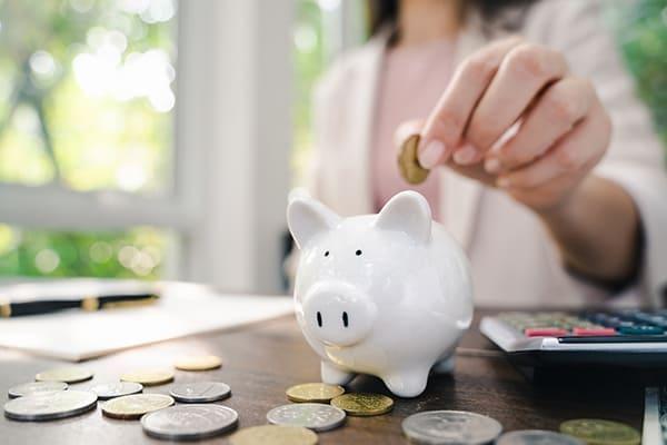 Frau schmeißt Münze in Sparschwein.