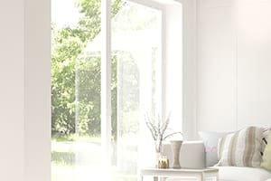 helles Wohnzimmer mit Couch und großem Fenster.