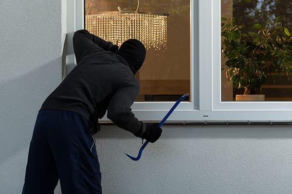 Einbrecher steht vor Wohnzimmerfenster