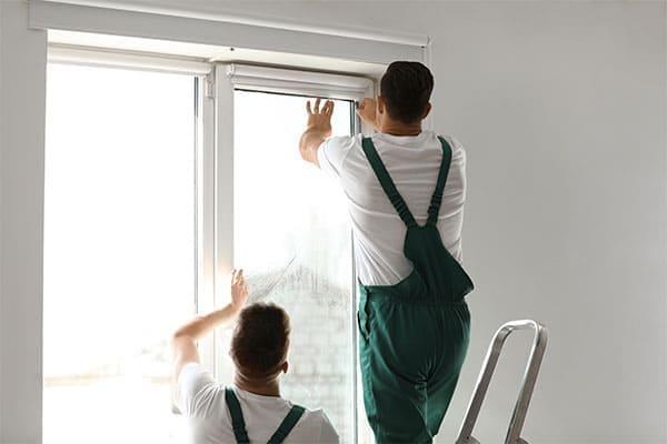 Fenstermonteure die eine Folie aufkleben
