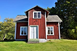 Großes Gartenhaus mit roter Holzfassade.
