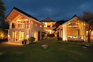 Villa super schön beleutet in der Nacht mit großen Fensterflächen.
