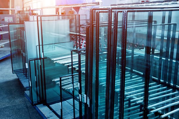 Lose Glasscheiben für Fensterelemente stehen aufrecht auf Glasböcke im Werk.