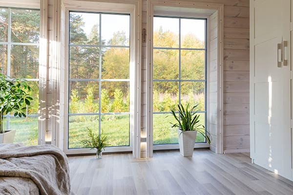 Schlafzimmer mit großen Fensterfronten mit Sprossenglas.