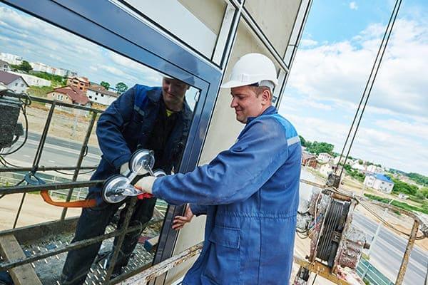 Aluminium Fenster von außen mit Bauarbeiter der Fensterscheibe einsetzt.