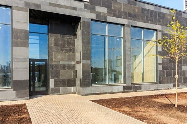 graues Gebäude mit neuen Glasscheiben von außen gesehen