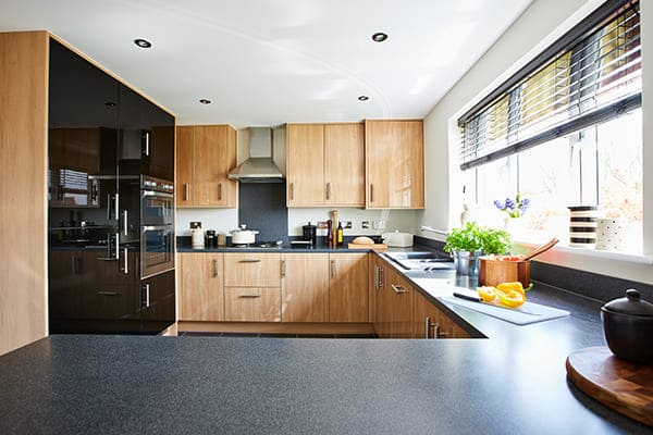 Moderne Luxusküche mit großem Fenster und Plissee.