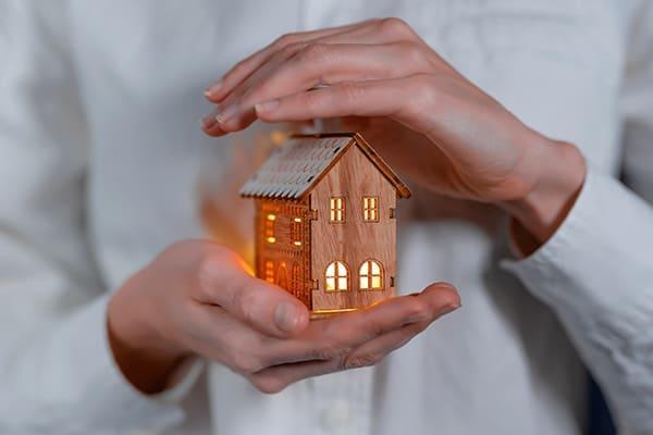 Haus in fürsorglichen weiblichen Händen mit Licht innen drin.
