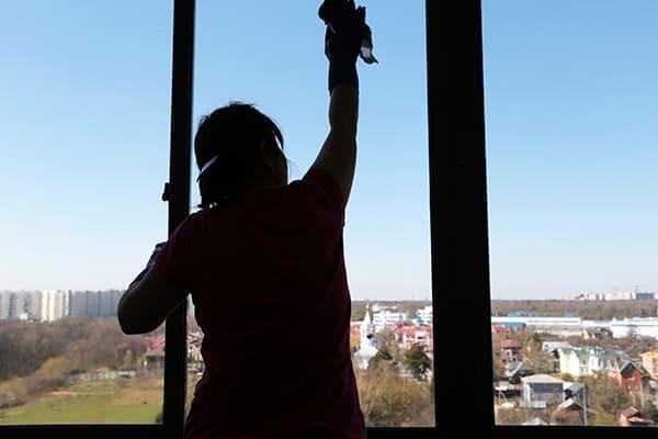 Frau putzt schönes großes Fenster von innen.