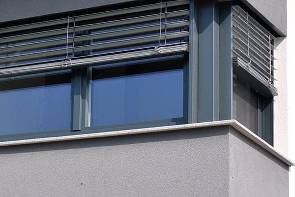 Graue Hauswand mit über Eck gekoppelte Fenster und Raffstore